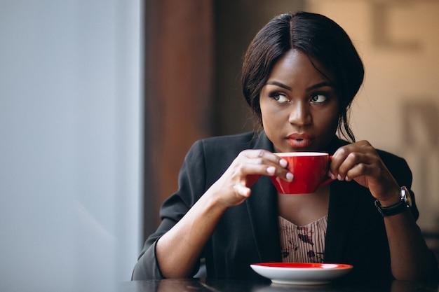 Mulher americana africana, café bebendo, uma barra