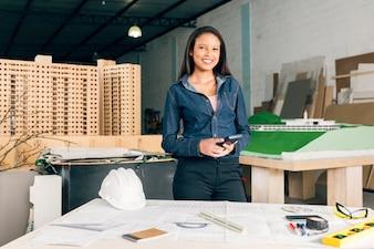 Mulher americana africana, com, calculadora, perto, tabela, com, capacete segurança, e, equipamentos
