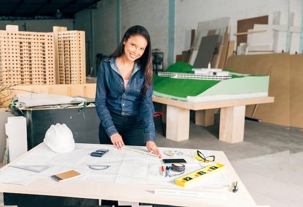 Mulher americana africana, com, régua, ligado, tabela, perto, capacete segurança, e, equipamentos