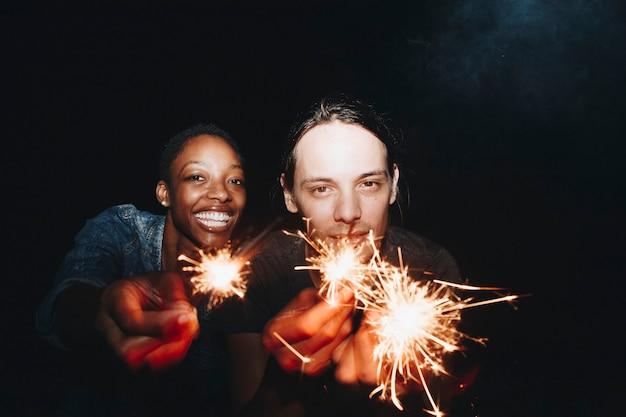 Mulher americana africana, e, um, homem caucasiano, par jogando, com, sparklers, celebração