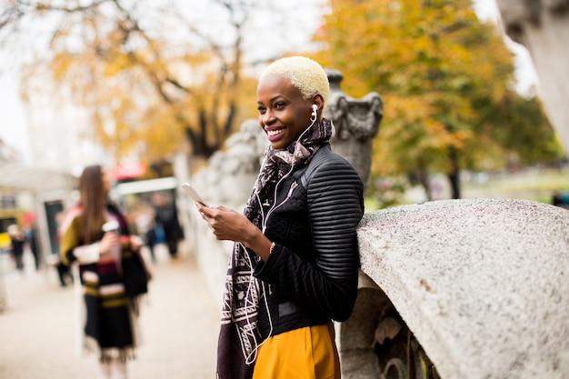 Mulher americana africana, posar, exterior, com, telefone móvel, e, um, xícara café, ir, em, autum