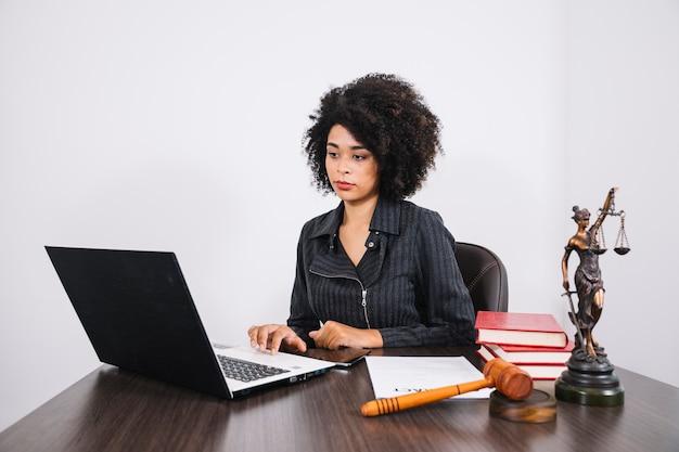 Mulher americana africana, usando computador portátil, tabela, perto, smartphone, livros, documento, e, estátua