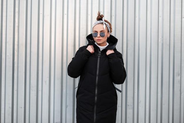 Mulher americana bonita jovem hippie com um elegante casaco preto de inverno com uma mochila de couro com uma bandana em óculos de sol perto de um edifício de metal. garota legal em uma caminhada.