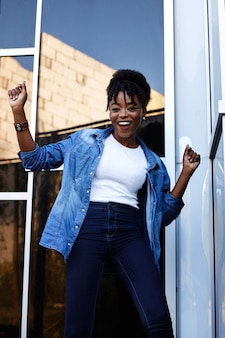 Mulher americana de pele escura está feliz e dançando em um espaço azul