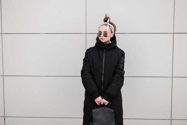 Mulher americana na moda jovem hippie com um elegante casaco preto de inverno longo com uma mochila de couro com uma bandana em óculos de sol perto de um edifício moderno. menina na moda em uma caminhada.