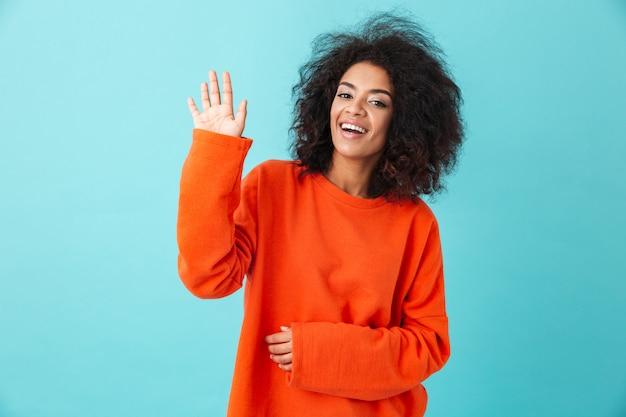 Mulher americana satisfeita na camisa colorida, sorrindo e dando as boas-vindas com a mão acenando, isolada sobre a parede azul
