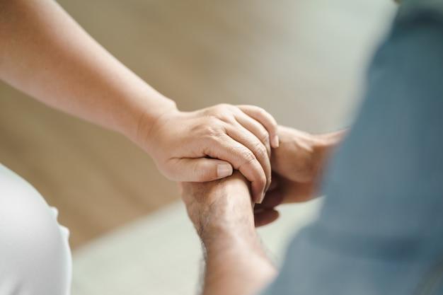 Mulher amiga ou família sentada e de mãos dadas durante animar o homem deprimido mental, psicólogo fornece ajuda mental ao paciente. conceito de saúde mental ptsd