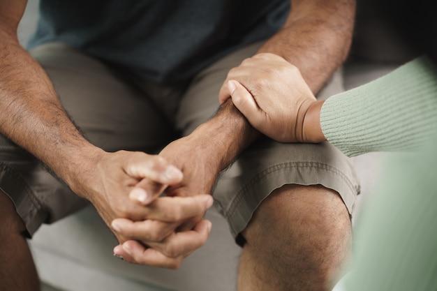 Mulher amiga ou família sentada e de mãos dadas durante animar o homem deprimido mental.