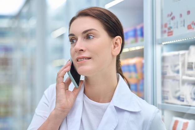 Mulher amigável com jaleco falando no smartphone