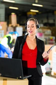 Mulher amigável, despachante ou supervisor usando fone de ouvido e laptop no armazém da empresa de encaminhamento,