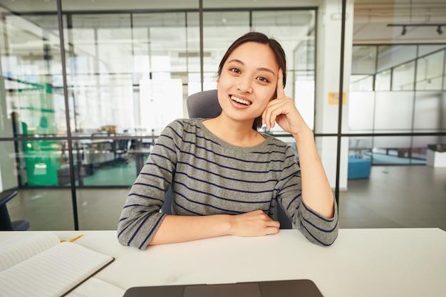 Mulher amigável em sua mesa com notebook e computador