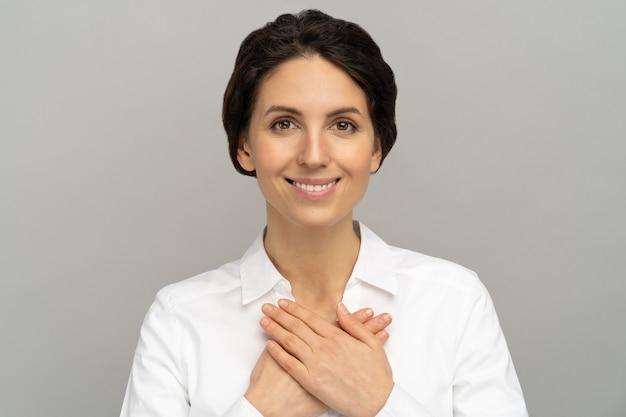 Mulher amigável segura as mãos no peito, sente-se grata pelo amor, pela apreciação, agradecida e pelo apoio