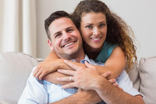 Mulher amorosa, abraçando o homem em casa