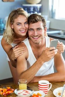 Mulher amorosa com homem segurando o celular em casa