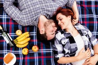 Mulher amorosa com o marido deitado no cobertor com muitas frutas