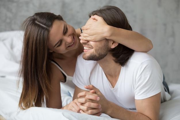 Mulher amorosa fechar os olhos do homem com as mãos tocando na cama