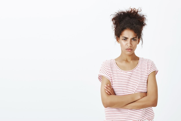 Mulher amuada com um penteado afro posando no estúdio