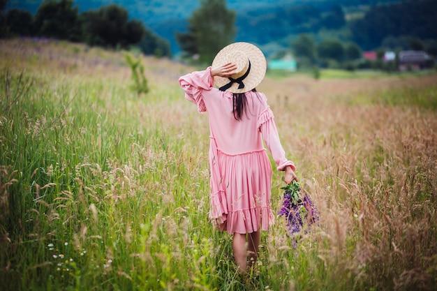 Mulher anda com buquê de lavander em campo verde