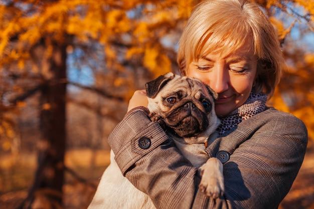 Mulher andando cão pug no parque outono. senhora feliz, abraçando o animal de estimação. melhores amigos