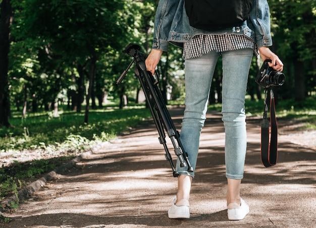 Mulher andando carregando um tripé e câmera na floresta