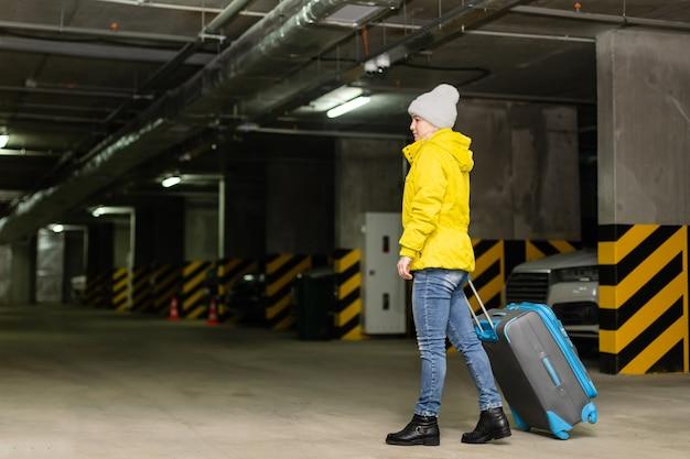 Mulher andando com bolsa no estacionamento subterrâneo