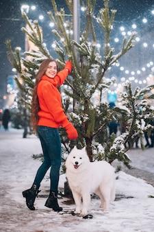 Mulher andando com cachorro branco