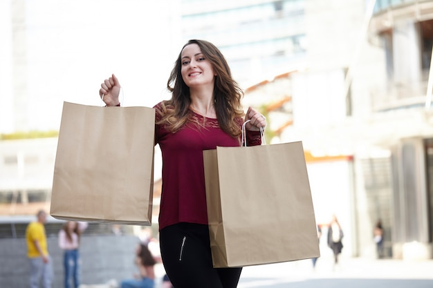 Mulher andando com sacolas de compras