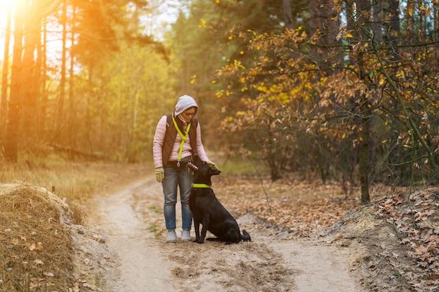 Mulher andando com seu cachorro na floresta de outono