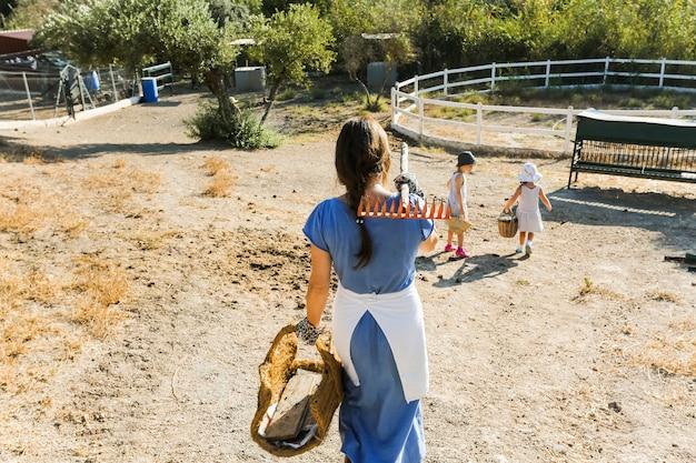 Mulher andando com suas filhas no campo