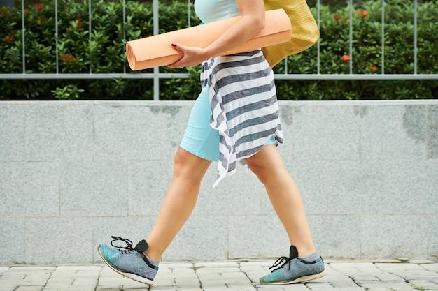Mulher andando com tapete de ioga