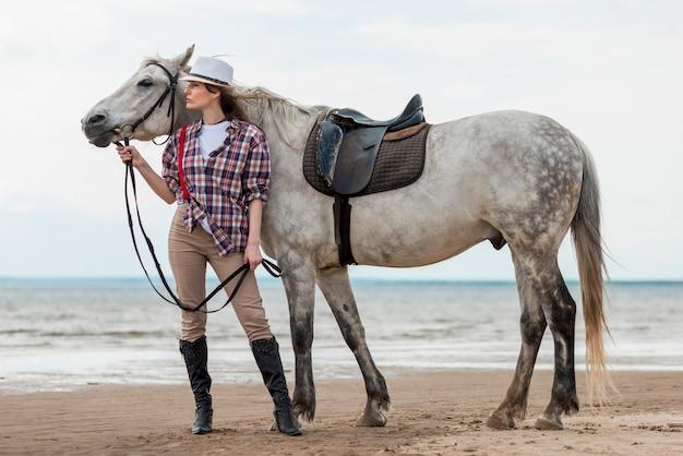 Mulher andando com um cavalo na praia