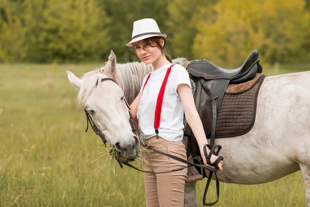 Mulher andando com um cavalo na zona rural