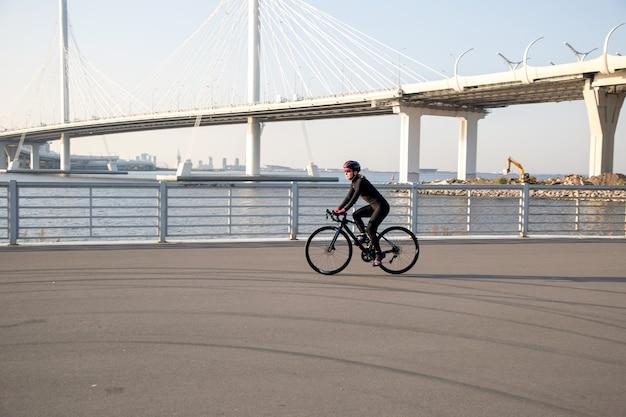 Mulher andando de bicicleta ao longo do aterro contra o fundo da ponte