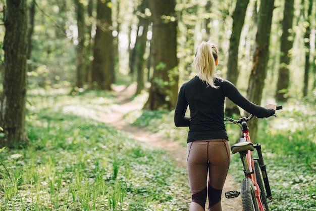 Mulher andando de bicicleta de montanha na floresta