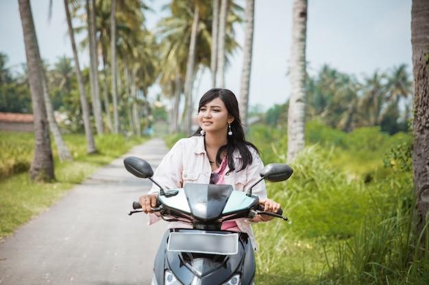 Mulher andando de bicicleta de scooter na estrada rural tropical