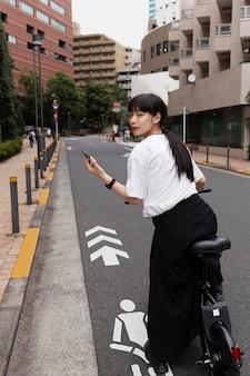 Mulher andando de bicicleta elétrica na cidade e segurando um smartphone