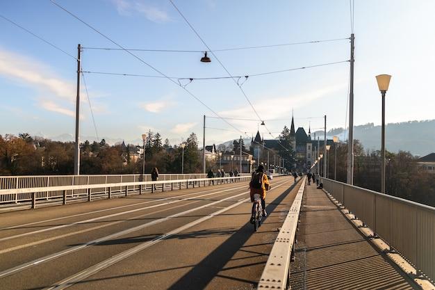 Mulher andando de bicicleta na ponte e o museu einstein ao fundo em berna em um dia ensolarado na suíça