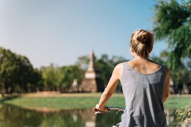 Mulher andando de bicicleta, olhando para a arquitetura na natureza, sem foco