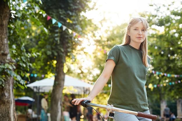 Mulher andando de bicicleta. retrato de jovem sentado em uma bicicleta, confuso e sorrindo em um parque da cidade