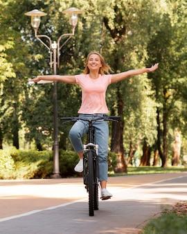 Mulher andando de bicicleta sem segurá-la