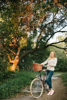 Mulher andando de bicicleta vintage com cesta