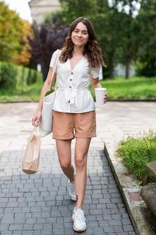 Mulher andando de frente com uma sacola de compras