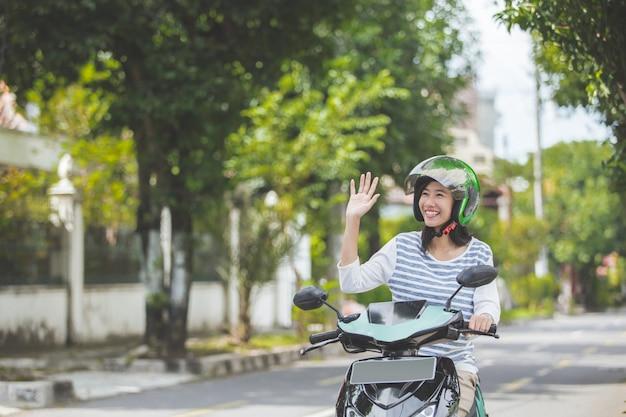 Mulher andando de moto e acenando a mão