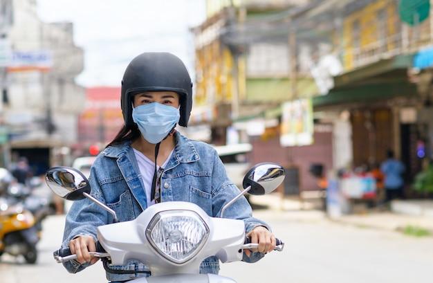 Mulher andando de moto usando uma máscara na cidade.