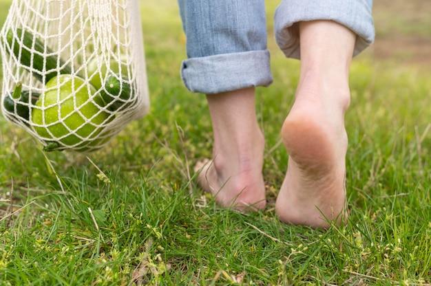Mulher andando descalço na grama com saco reutilizável