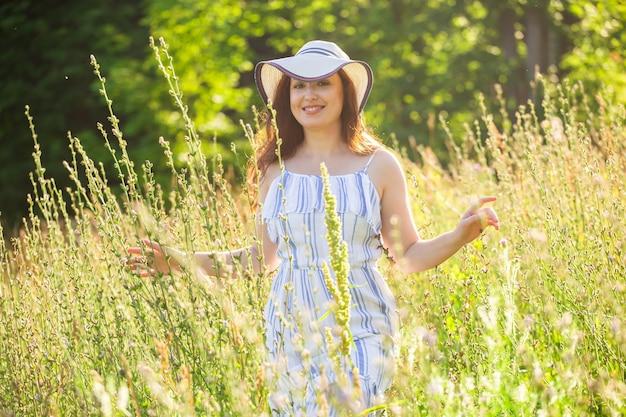 Mulher andando em um campo em um dia ensolarado de verão.