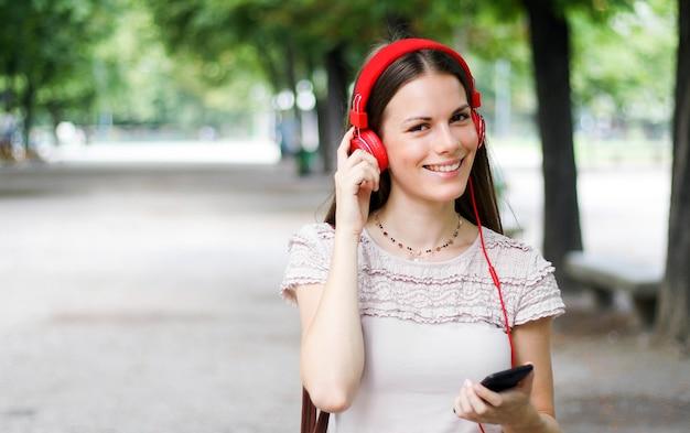 Mulher andando em um parque enquanto estiver usando seu smartphone para ouvir música