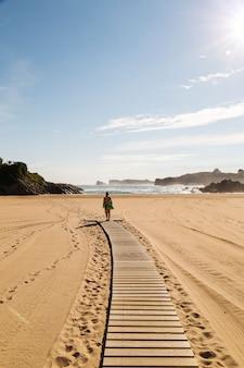 Mulher andando na areia de uma praia linda