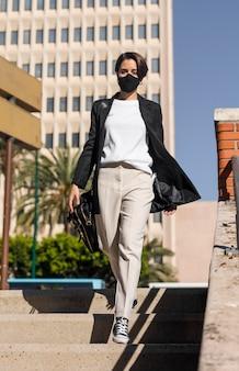 Mulher andando na cidade usando uma máscara médica