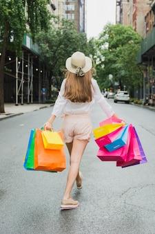 Mulher andando na estrada com sacolas coloridas